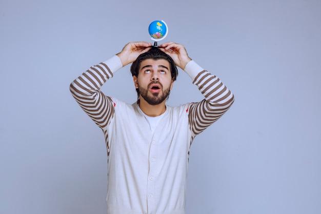 Mężczyzna trzyma mini kulę ziemską nad głową.