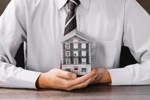 Mężczyzna trzyma miniaturowego dom w rękach