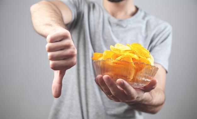 Mężczyzna trzyma miskę chipsów ziemniaczanych i robi kciuk w dół.