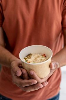 Mężczyzna trzyma miskę darowanej żywności