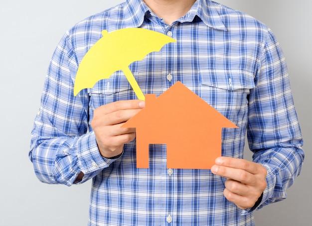 Mężczyzna trzyma model domu. koncepcja ubezpieczenia domu
