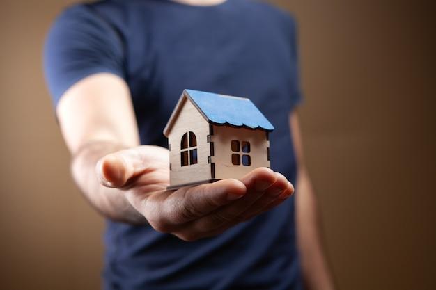Mężczyzna trzyma model domu na brązowym tle