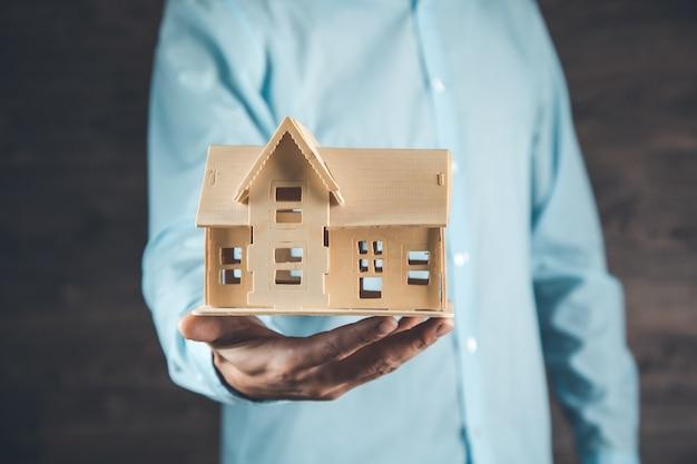 Mężczyzna trzyma model domu na ciemnym tle