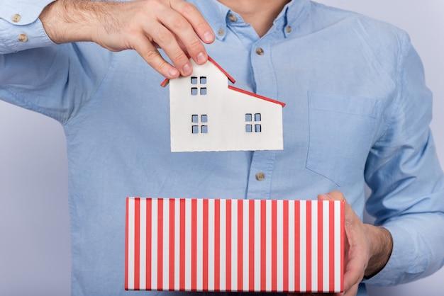 Mężczyzna trzyma modela dom i pudełko. model domu w otwartym kartonie