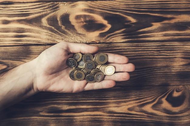 Mężczyzna trzyma monety na drewnianym stole