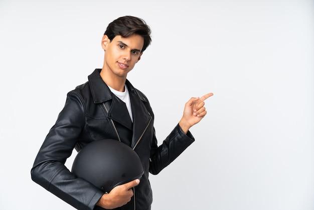 Mężczyzna trzyma motocykl hełma wskazuje palec z boku