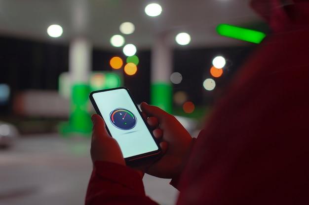 Mężczyzna trzyma na ekranie smartfona z cyfrowym licznikiem paliwa na tle nocnej stacji benzynowej do samochodu.