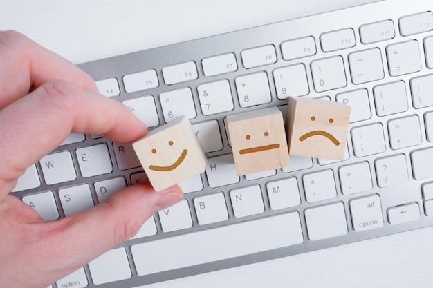 Mężczyzna trzyma na klawiaturze drewniany sześcian z wizerunkiem pozytywnej twarzy obok negatywnych i neutralnych emocji.