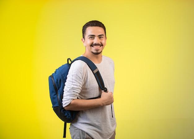 Mężczyzna trzyma niebieski plecak i uśmiecha się.