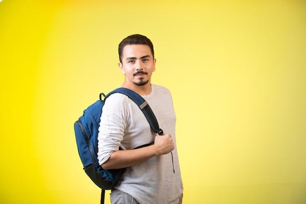 Mężczyzna trzyma niebieski plecak i wygląda zalotnie.