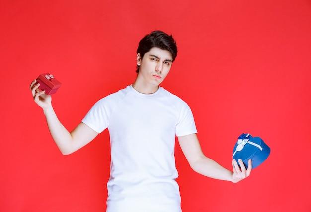 Mężczyzna trzyma niebieskie i czerwone pudełka na prezenty i wygląda na zdezorientowanego.