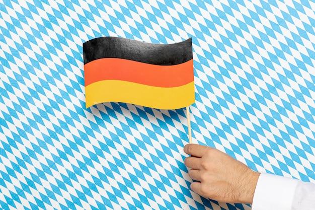 Mężczyzna trzyma niemiec flaga z wzorzystym tłem