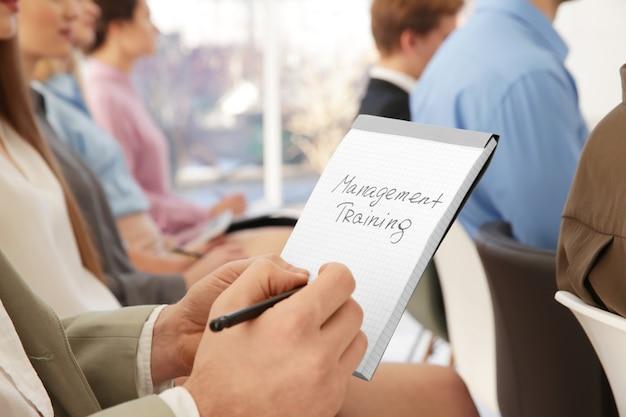 Mężczyzna trzyma notebook z tekstem szkolenia zarządzania w prezentacji biznesowej