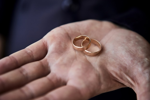 Mężczyzna trzyma obrączki ślubne, pan młody przygotowuje się rano przed ceremonią