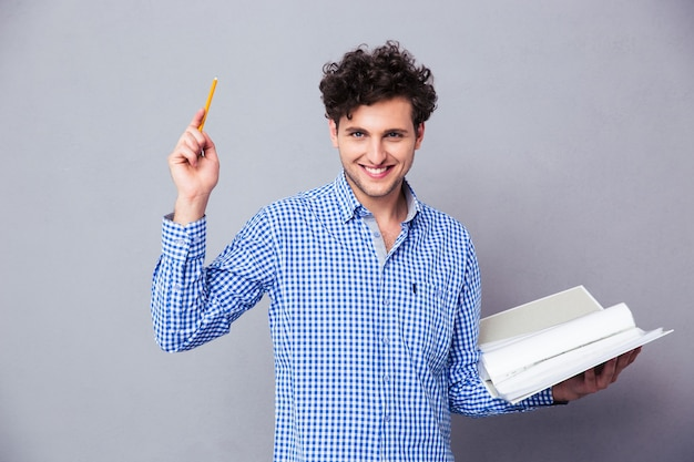 Mężczyzna trzyma ołówek i folder z plikami