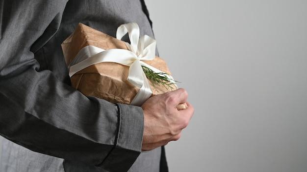Mężczyzna trzyma opakowanie na prezent na szarym tle.