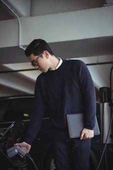 Mężczyzna trzyma organizator podczas ładowania samochodu elektrycznego