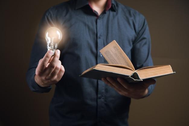 Mężczyzna trzyma otwartą książkę i żarówkę. pomysł z książki from
