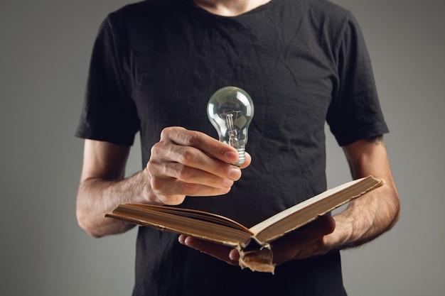 Mężczyzna trzyma otwartą książkę i żarówkę. pomysł z książki