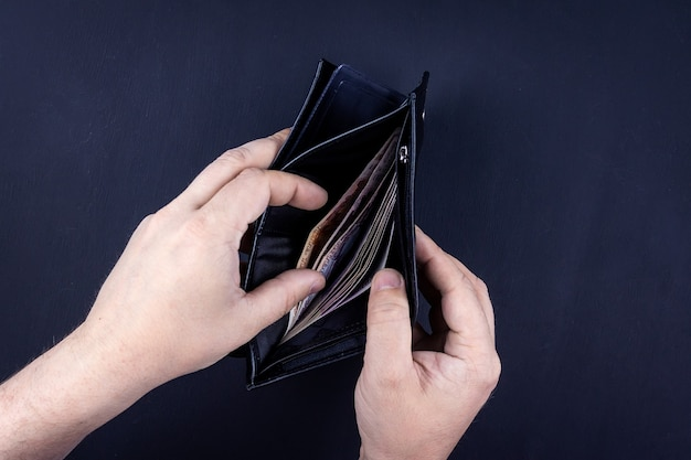 Mężczyzna trzyma otwarty portfel z pieniędzmi w rękach.