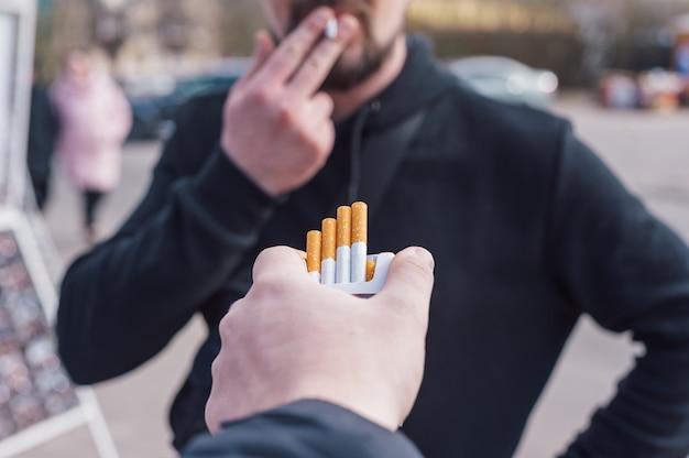 Mężczyzna trzyma paczkę papierosów na tle palącego mężczyzny.