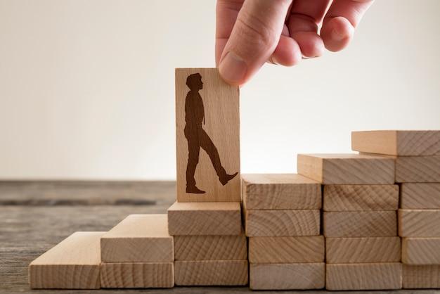 Mężczyzna trzyma palcami drewniany domino w kształcie biznesmena, wchodząc po schodach, aby wspiąć się po drabinie kariery.