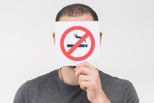 Mężczyzna trzyma palenie zabronione znak przed jego twarzą przeciw białemu tłu