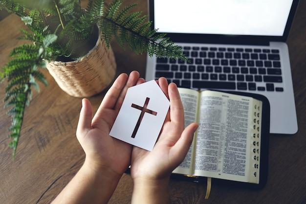 Mężczyzna trzyma papierową ikonę kościoła modląc się przez wiarę z laptopem komputerowym, koncepcja usług kościelnych online, koncepcja kościoła online w domu, duchowość i religia.
