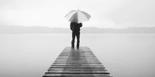 Mężczyzna trzyma parasol na molo nad spokojnym jeziorem.