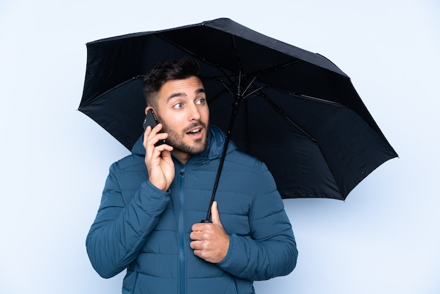 Mężczyzna trzyma parasol nad odosobnioną ścianą
