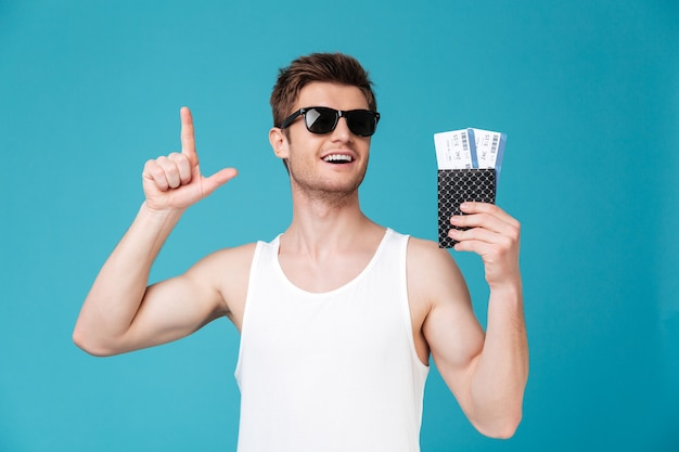 Mężczyzna trzyma paszport z biletami w okularach przeciwsłonecznych