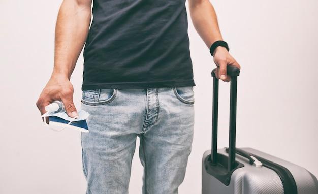 Mężczyzna trzyma paszport z biletem kolejowym i maską medyczną w ręku