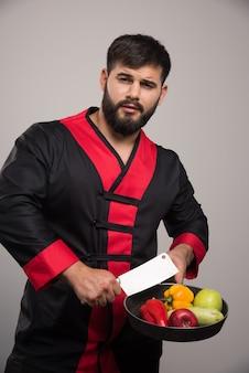 Mężczyzna trzyma patelnię z warzywami i nożem.