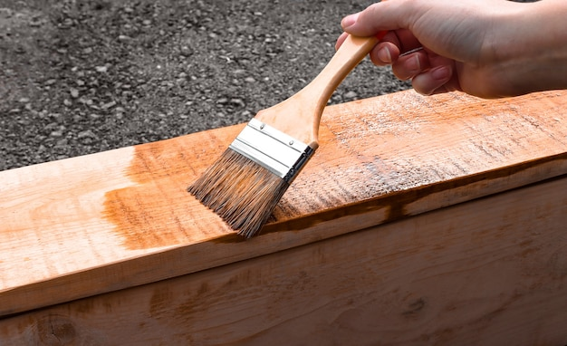 Mężczyzna trzyma pędzel do malowania drewna w swoich pracach domowych, pokrywając drewniany produkt farbami
