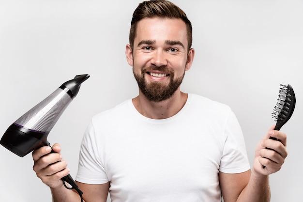 Mężczyzna trzyma pędzel i suszarkę do włosów