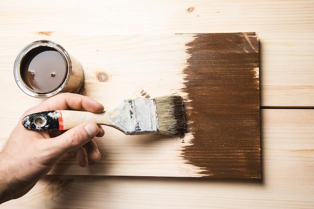 Mężczyzna trzyma pędzel na drewnie