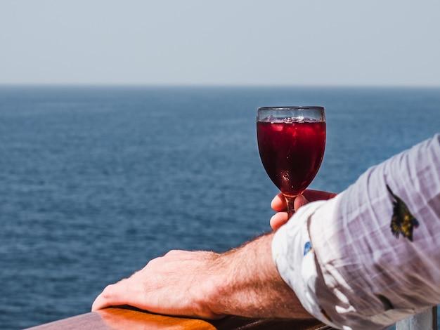 Mężczyzna trzyma piękną lampkę różowego wina