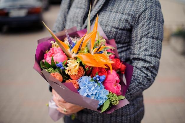Mężczyzna trzyma piękny jasny i kolorowy bukiet kwiatów