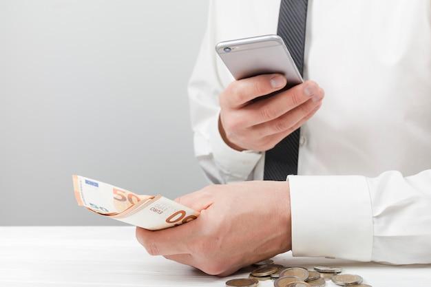 Mężczyzna trzyma pieniądze i używa kalkulatora
