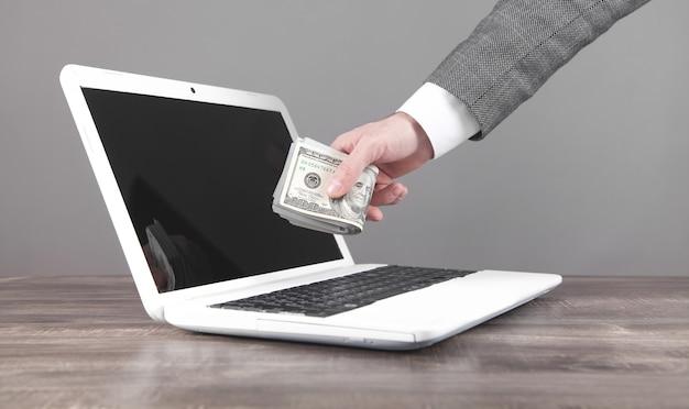 Mężczyzna trzyma pieniądze na laptopie