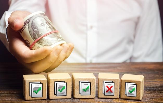 Mężczyzna Trzyma Pieniądze Nad Blokami Z Dokumentami Zezwoleń Sztuczne Przeszkody Biurokratyczne Premium Zdjęcia