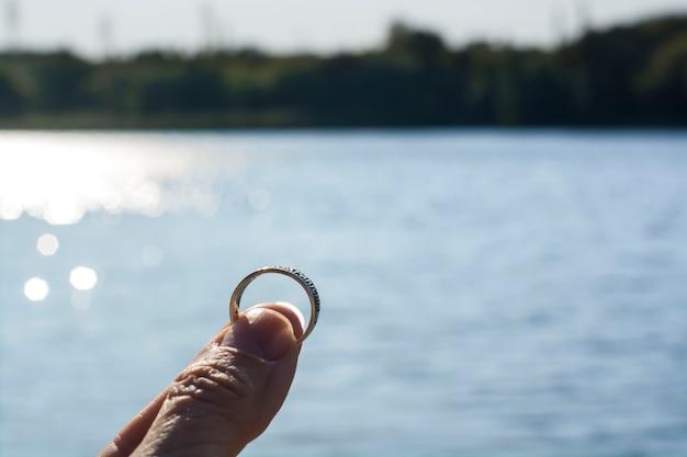 Mężczyzna trzyma pierścionek w palcach