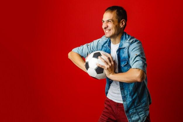 Mężczyzna trzyma piłkę na kolorowe tło