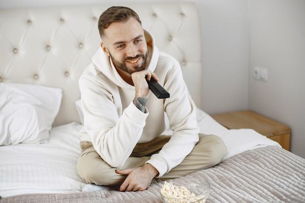 Mężczyzna trzyma pilota z miską popcornu