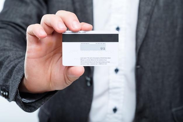 Mężczyzna trzyma plastikową kartę. oszustwo z wykorzystaniem karty kredytowej. ochrona danych osobowych.