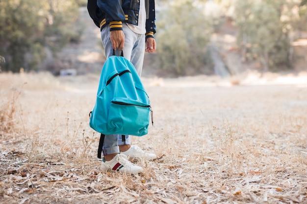 Mężczyzna trzyma plecak w parku