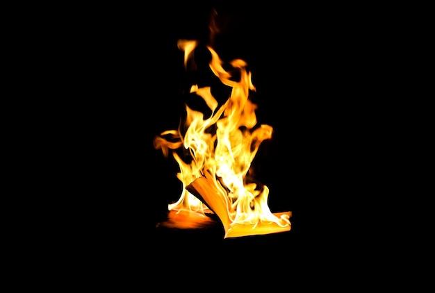 Mężczyzna trzyma płonącą książkę w ogniu w nocy. ludzie nie lubią czytać. problemy intelektualne.