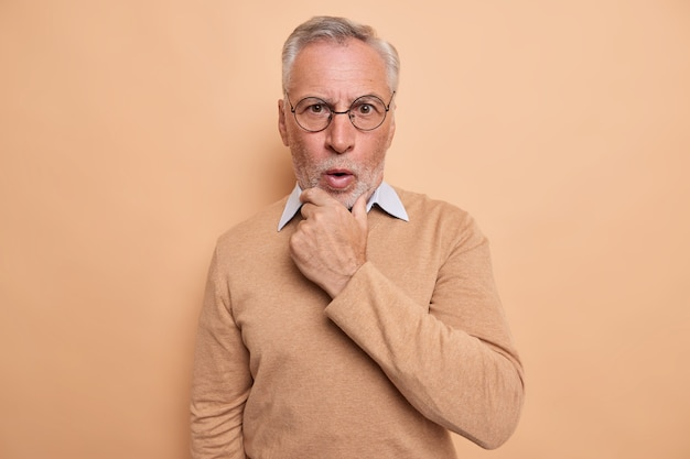 Mężczyzna trzyma podbródek reaguje emocjonalnie na wiadomości wygląda na zszokowany aparatem nosi optyczne okrągłe okulary swobodny sweter na brązowym tle