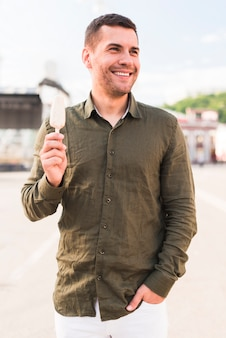 Mężczyzna trzyma popsicle patrzeje daleko od i ono uśmiecha się
