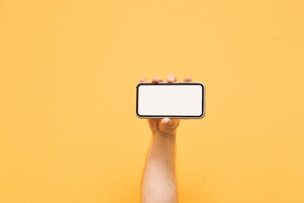 Mężczyzna trzyma poziomo odwrócony smartfon z czystym białym ekranem na żółtym